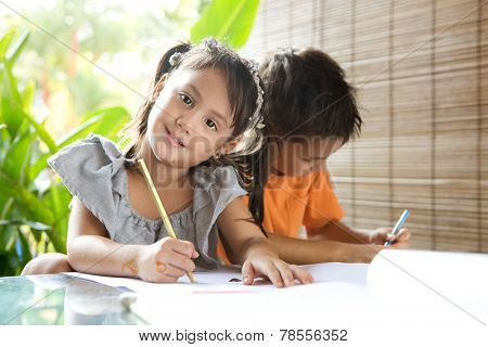 Cute ?little pan asian girl holding a coloring pencil sitting next to an older brother engrossed in coloring activity in home environment