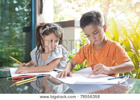 Cute little pan asian boy coloring his drawing while sitting while being watched by his curious younger sister in home environment