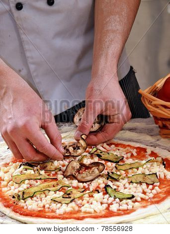 Adding ingredients on pizza.