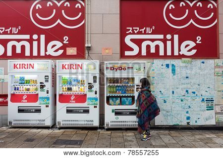 OSAKA, JAPAN - 30 NOVEMBER 2014: A young girl checks out the beverage vending machines in Osaka city. Unmanned vending machines selling snacks, cigarettes and beverages are common in Japan.