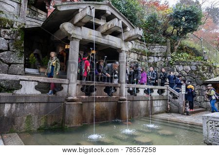 KYOTO, JAPAN: DECEMBER 1, 2014: Tourist and devotees visit the Otowa waterfall at the Kiyomizu-dera temple. This temple was established in 778 and is listed on the UNESCO World Cultural Heritage List.