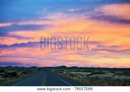 Sunset in Patagonia. Flat plain, rough dirt road and red sky