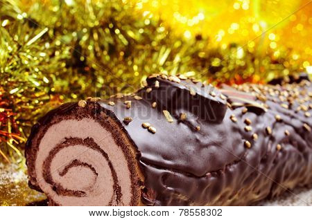 a yule log cake, traditional of christmas time, on a festive table ornamented with shiny tinsel