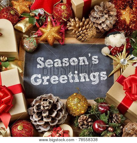 the text seasons greetings written in a chalkboard surrounded by some gifts and a pile of different christmas ornaments, such as baubles, stars and pine cones