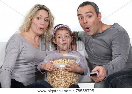 A nice family watching a movie.