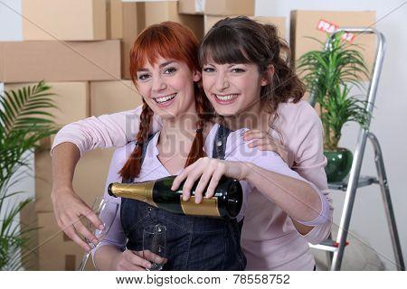 Two female flat-mates celebrating move