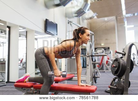 fitness, sport, training and people concept - smiling woman with dumbbell flexing muscles on bench in gym