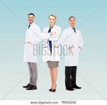 healthcare, profession and medicine concept - group of smiling doctors in white coats over blue background