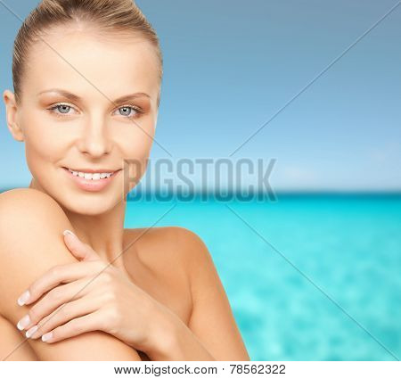 beauty, people and health concept - beautiful young woman with bare shoulders over blue water and sky background