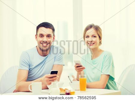 food, home, couple and technology concept - smiling couple with smartphones reading news and having breakfast at home
