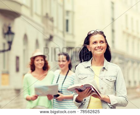 tourism, travel, leisure and holidays and friendship concept - smiling teenage girls with city guide, map and camera outdoors