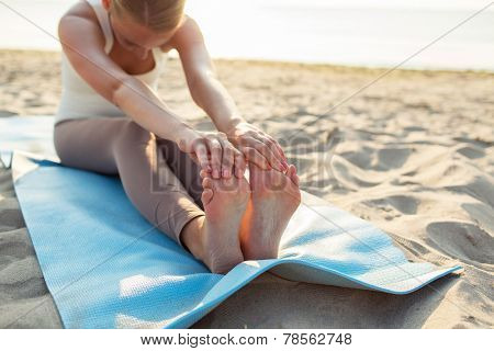 fitness, sport, people and lifestyle concept - close up of woman making yoga exercises on mat outdoors