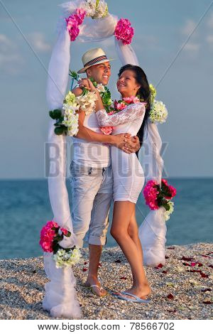 Groom with bride wearing lei  under archway on beach
