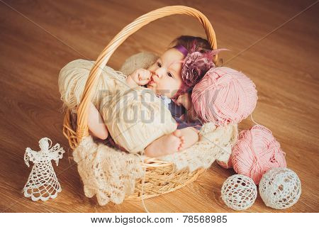 Newborn baby lying in a basket.