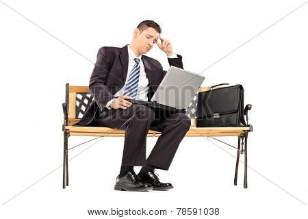Upset businessman working on a laptop seated on a bench isolated on white background