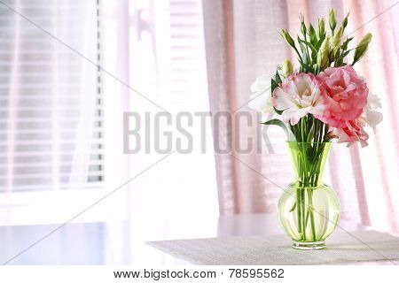 Beautiful flowers in vase with light from window