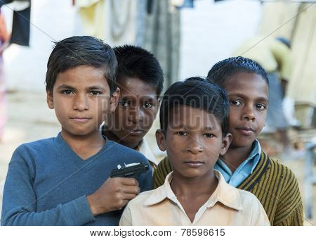 Four Boys, One Holding Toy Gun.