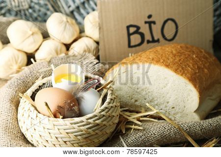 Eggs, bread and fresh milk in glass jug with inscription BIO  , on wooden background. Organic products concept