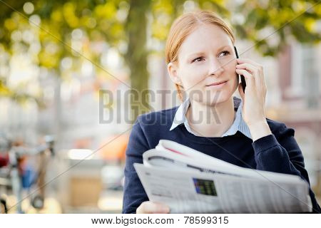 Woman With Newspaper And Mobile Phone