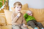 picture of pretty-boy  - Two little brother boys watching tv and eating candy indoor - JPG