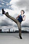 stock photo of martial arts girl  - A female athlete performing a turning kick in a dramatic city cloudscape - JPG