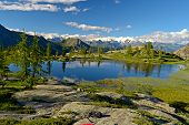 stock photo of italian alps  - High altitude mountain lake at sunset in idyllic uncontaminated environment - JPG