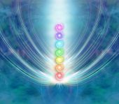 stock photo of kundalini  - Ethereal blue energy formation background with a central column of the seven chakras in a beam of spiraling light - JPG