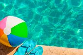 stock photo of pool ball  - turquoise flip flops and ball on the edge of the pool - JPG
