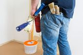 pic of roller door  - Man holding rollers and brushes while renovating home - JPG