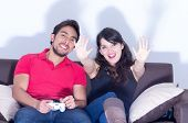 stock photo of indoor games  - young cute couple playing video games having fun in livingroom - JPG