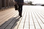 stock photo of down jacket  - A waist down picture of a woman wearing a plaid jacket holding a purse walking on a sidewalk with her shadow behind her - JPG