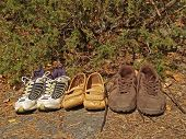Three pairs of tourist shoes poster