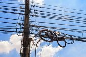 stock photo of untidiness  - electricity post with untidy wire and blue sky - JPG