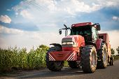 foto of machinery  - farming tractor with machinery on a rural road - JPG