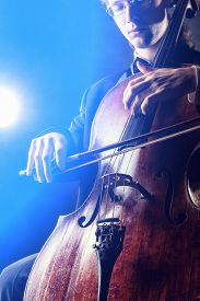 pic of cello  - Cellist playing classical music on cello on black background - JPG