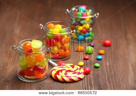 Colorful candies in jars on wooden background