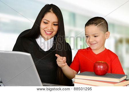 Teacher and her pupil looking at laptop