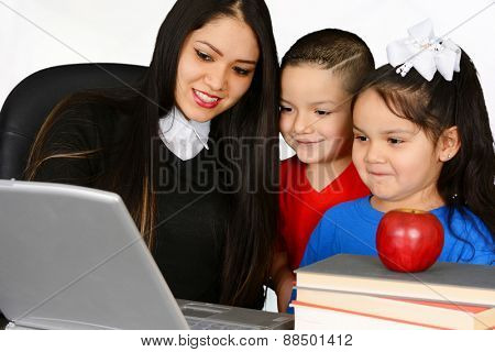 Young teacher and her pupils looking at laptop