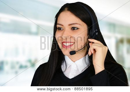 Young brunette businesswoman talking on the headset