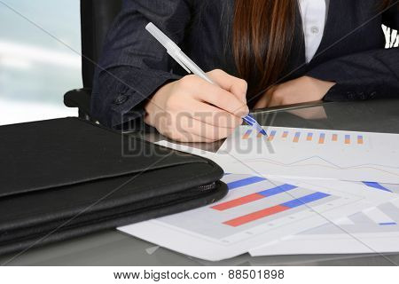 Female manager analyzing business data charts in the office