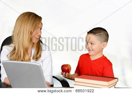Schoolboy giving red apple to his teacher