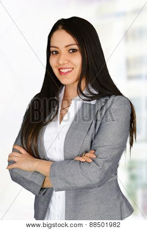 Young business woman standing with hands crossed, looking at the camera