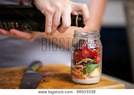 Making a delicious healthy salad in a jar with apples, seeds and nuts, leaves and cherry tomatoes