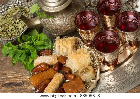 Moroccan tea tray with mint leaves and ramadan cookies and dates