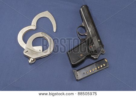 gun, magazine and police handcuffs lying on the table