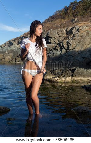 Beautiful woman with wet hair posing on a rocky beach