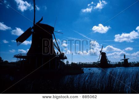 Silhouettes Of Three Classic Windmills.