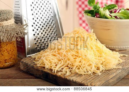 Grated cheese on wooden cutting board in kitchen