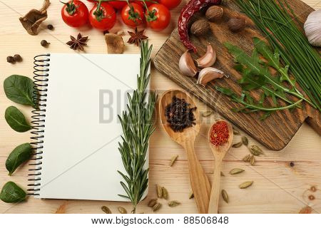 Open recipe book with fresh herbs, tomatoes and spices on wooden background