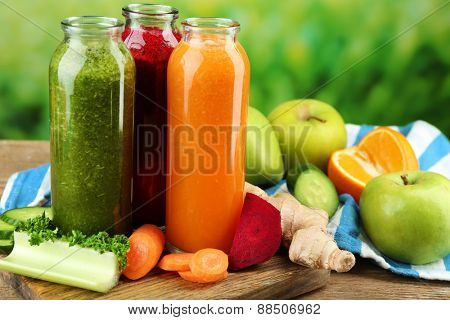 Assortment of healthy fresh juices in glass bottles on wooden table, on bright background